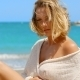 Blond Woman Sitting On Beach In Front Of Ocean - VideoHive Item for Sale