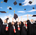 happy students throwing graduation caps into the Air - PhotoDune Item for Sale