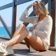 Blond Woman Wearing White Sweater On Ocean Pier - VideoHive Item for Sale