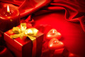 Valentine's Day. Red heart shaped candles and gift on red silk - PhotoDune Item for Sale