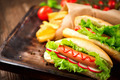 Hot dog. Grilled hot dogs with ketchup on a wooden table - PhotoDune Item for Sale