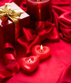 Valentine red heart shaped candles and gift on red silk - PhotoDune Item for Sale