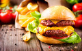 Cheeseburger with fresh salad and french fries on a wooden table - PhotoDune Item for Sale