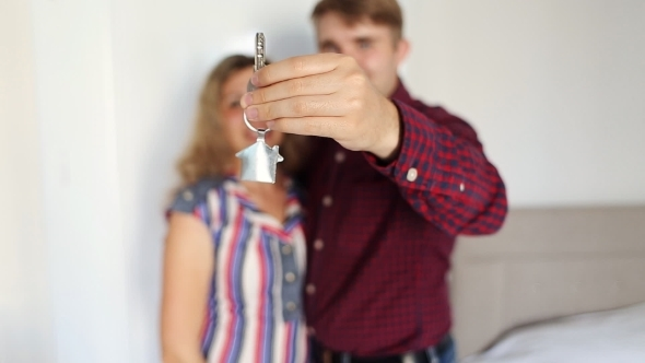 Happy Smiling Young Couple Showing a Pair Of Keys