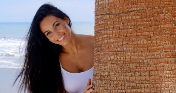 Pretty Lady Peeking Behind Tree Trunk At The Beach