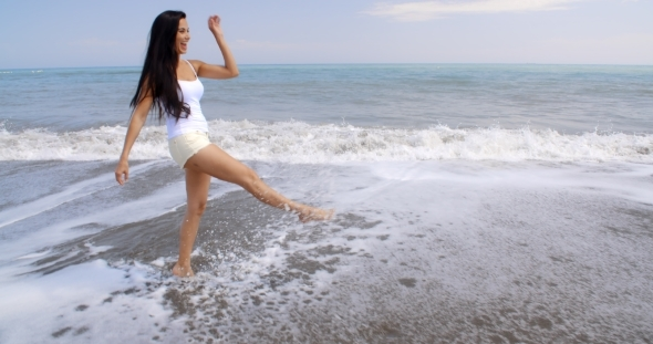 Carefree Woman Kicking Up Water On Tropical Beach