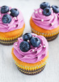 Tasty blueberry cupcakes decorated with cream and fresh berries