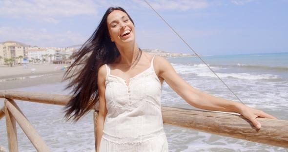 Woman At The Beach Railing Laughing At The Camera