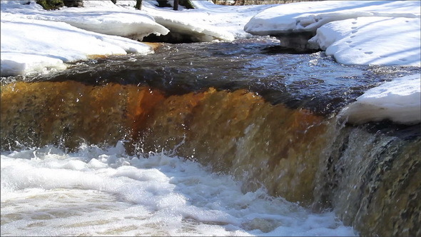 A Clear Water Flowing Between the Snow-Covered
