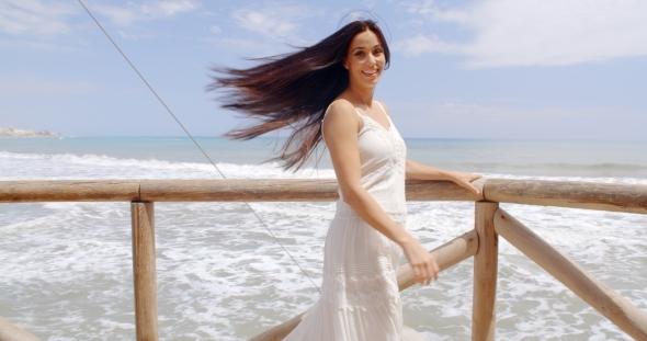 Lady Holding At Beach Railing With Air Blown Hair