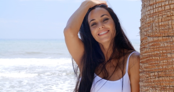 Smiling Woman At The Beach Leaning Against Tree