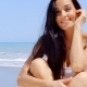 Portrait Of Woman Sitting In Sunshine On Beach - VideoHive Item for Sale