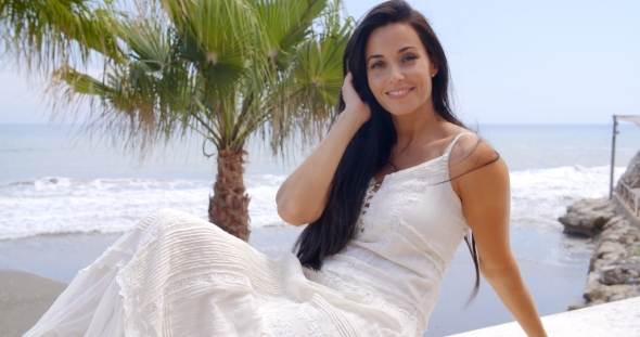 Pretty Woman In White Sitting On Terrace Rail