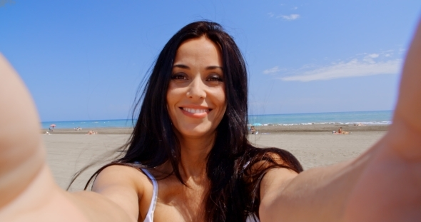 Brunette Woman Taking Self Portrait On Beach