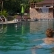 Woman Swimming In a Blue Pool On Luxury Summer - VideoHive Item for Sale
