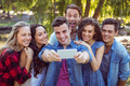 Happy friends taking a selfie on parkland