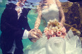 Bride and groom holding hands underwater