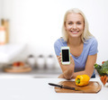 smiling woman with smartphone cooking vegetables
