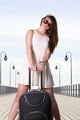 Beautiful woman girl on sea pier with suitcase