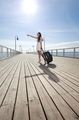 Beautiful woman elegant girl on a sea pier with suitcase