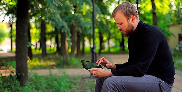 Man With the Tablet Computer on a Bench in a Park