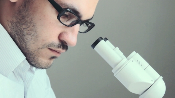 Young Male Doctor Viewing Through Microscope