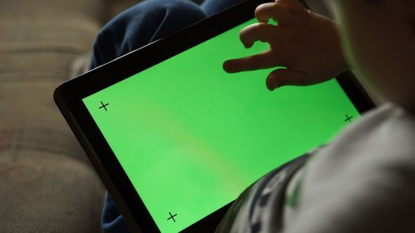 Child Is Using A Tablet PC With Green Screen