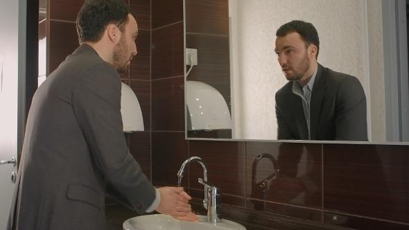 Businessman Washing Face In Bathroom