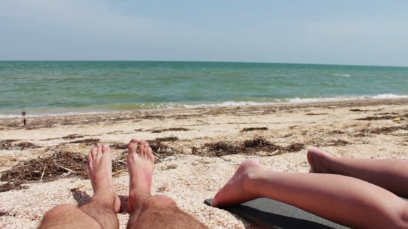 The Legs Of Two People Are Sunbathe On The Beach