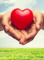 womans cupped hands showing red heart - PhotoDune Item for Sale