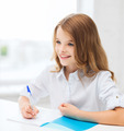 student girl writing in notebook at school - PhotoDune Item for Sale