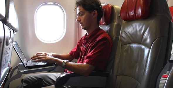Man Working on Laptop on Airplane 1