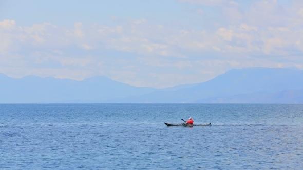 Man Rowing In Canoe In The Sea