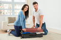 Couple Trying To Close Suitcase With To Much Clothes - PhotoDune Item for Sale