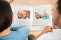 Couple Looking At Baby's Photo Album - PhotoDune Item for Sale