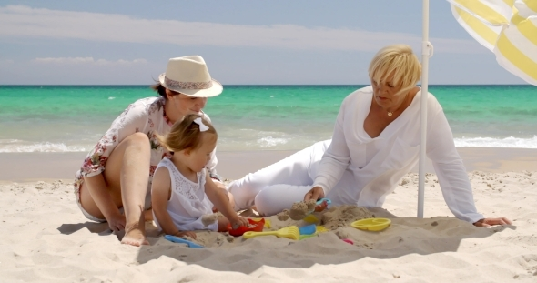 Small Family Having Fun At The Beach Sand