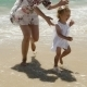 Little Girl Running Along a Beach With Her Mother - VideoHive Item for Sale