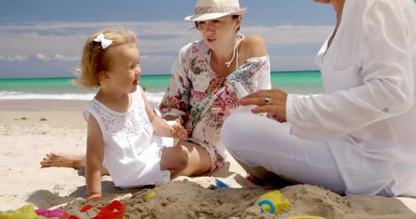 Girl Resting At The Beach With Mom And Grandma