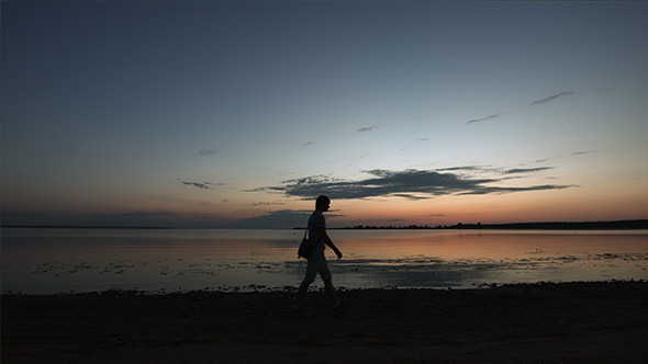 Young Man Walking in the Beach after Sunset