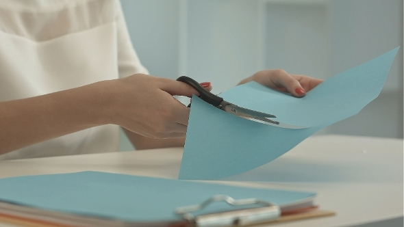 Girl Is Cutting Color Blue Paper With Scissors