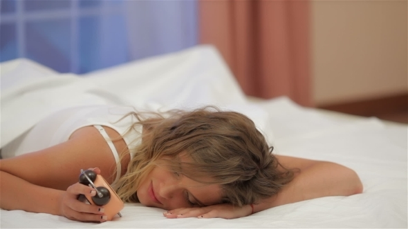 Beautiful Sad Girl In Bedroom With Alarm Clock