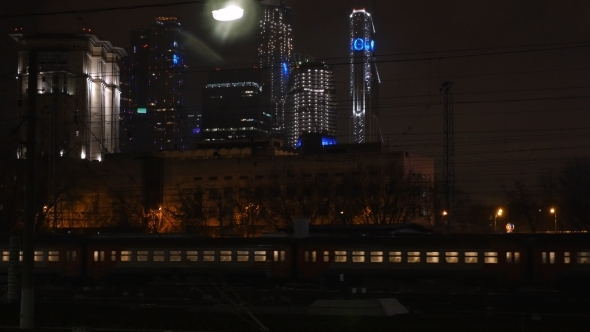 Passenger Train Passing Through The City At Night