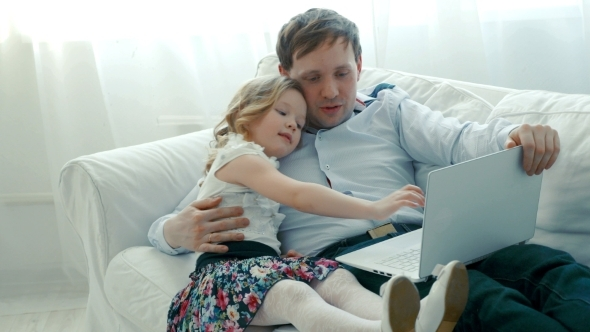 Father And Daughter Using Laptop On The Sofa