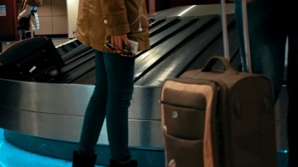 People Getting Luggage On Conveyer Belt