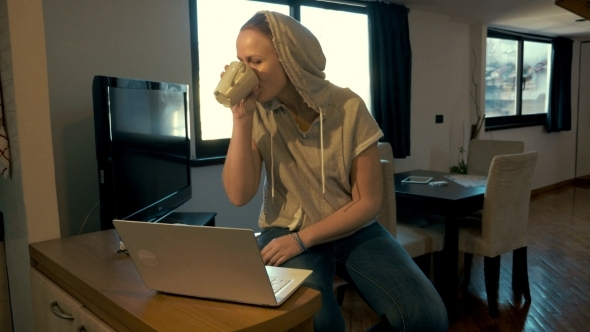 Woman At Home Chatting On Laptop And Drinking Tea