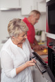 Middle Aged Woman Checking her Food In the Oven - PhotoDune Item for Sale