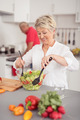 Happy Wife Preparing Fresh Salad at the Kitchen - PhotoDune Item for Sale