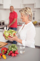 Happy Wife Holding Fresh Salad at the Kitchen - PhotoDune Item for Sale