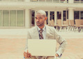 Business man with laptop skeptically looking at you camera - PhotoDune Item for Sale