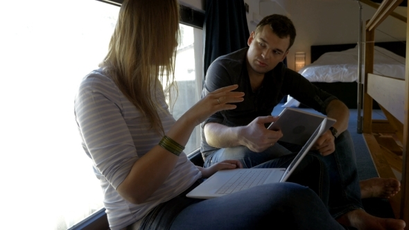 Man And Woman Talking While Using Pad And Laptop
